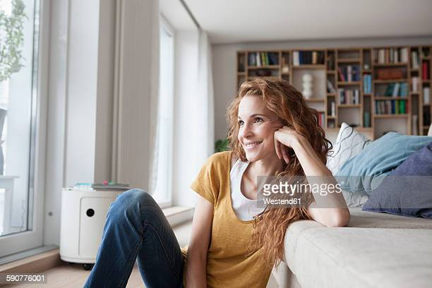 Smiling woman at home sitting on floor