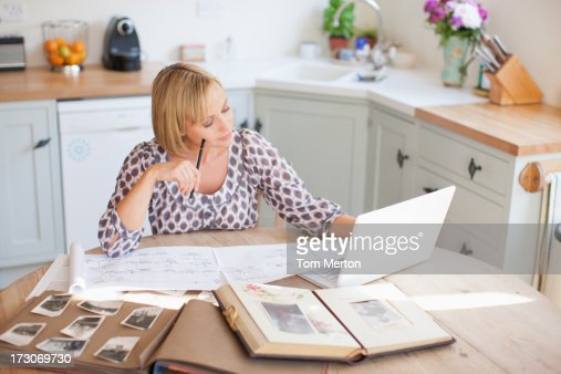 Smiling woman at table with old photographs and genealogical tree : Stock Photo