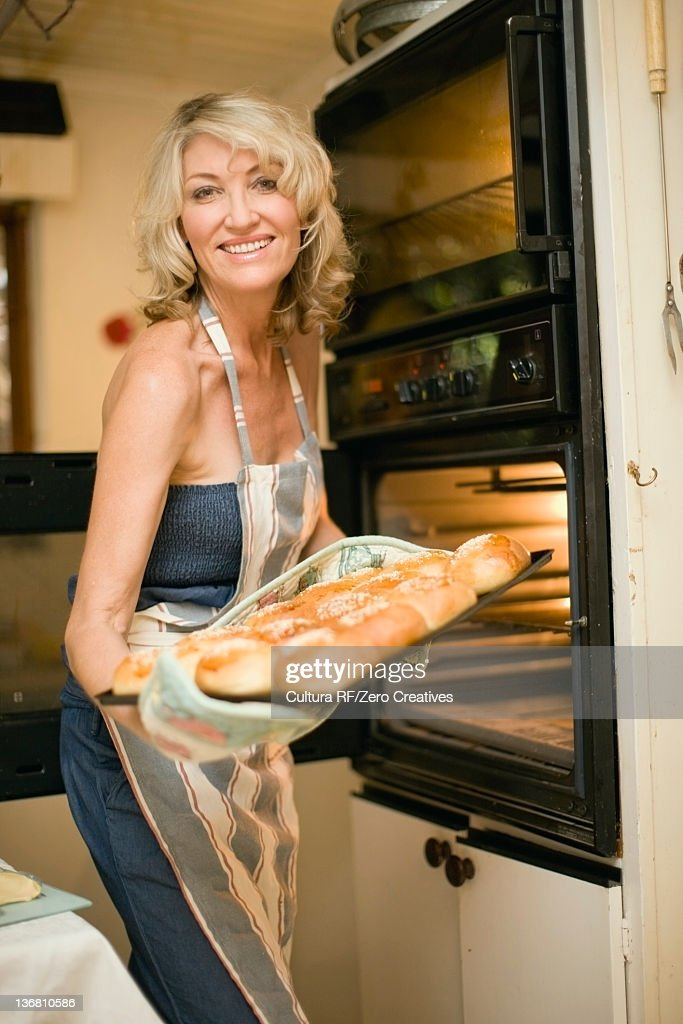 Smiling woman baking in kitchen : Stock Photo