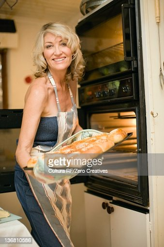 Smiling woman baking in kitchen : Foto de stock