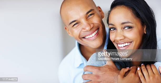 Smiling woman being embraced by her boyfriend