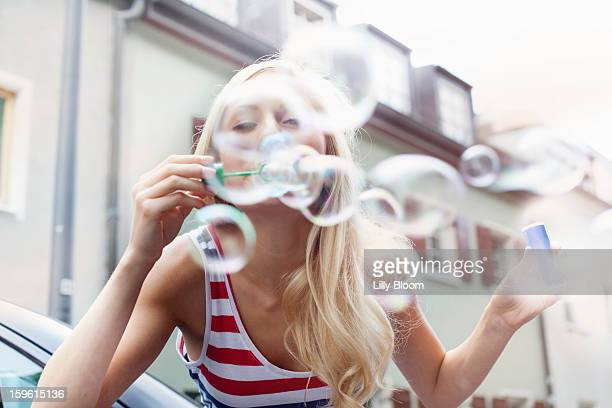 Smiling woman blowing bubbles outdoors