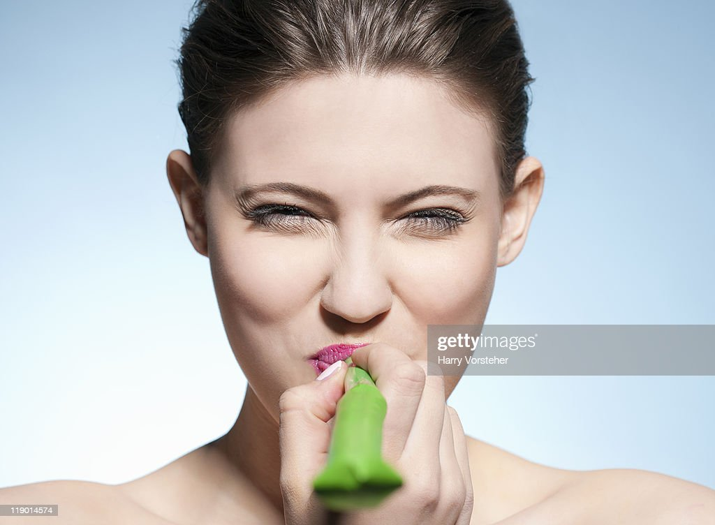 Smiling woman blowing noisemaker : Stock Photo