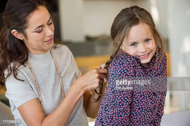 Smiling woman braiding her daughter's hair