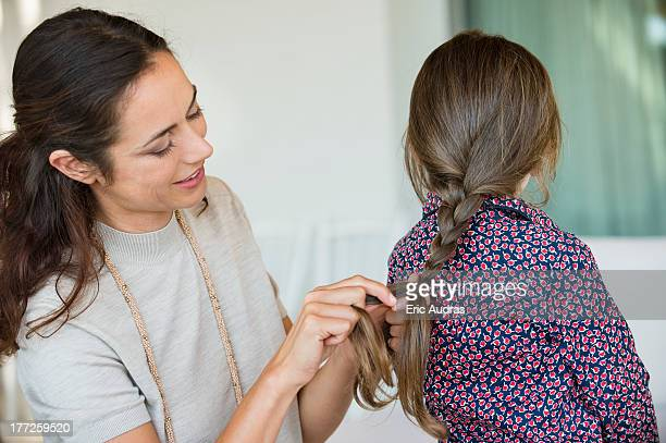 Smiling woman braiding her daughter's hair