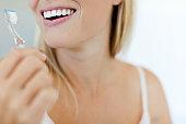 Smiling woman brushing teeth, cropped