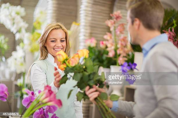Smiling woman buying roses in a flower shop.
