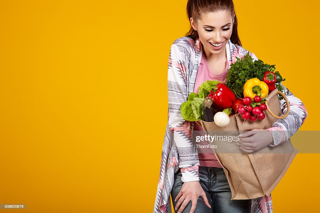 Smiling woman carrying a bag with vegetables : Stock Photo