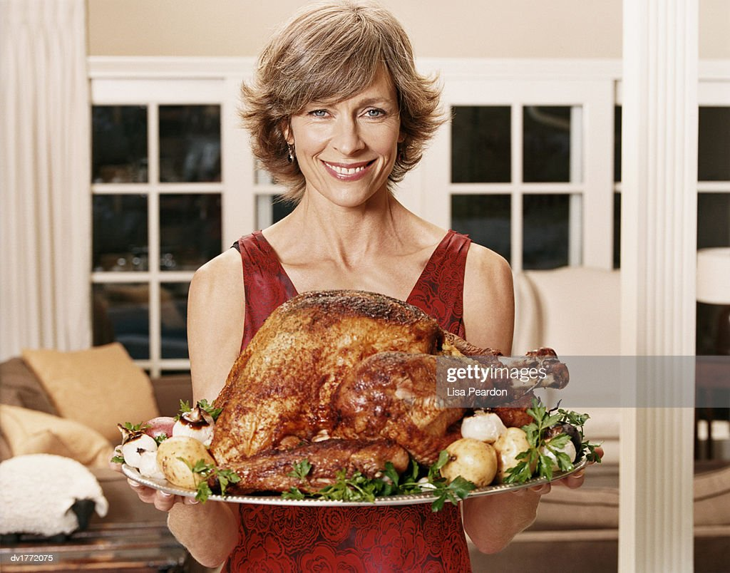 Smiling Woman Carrying a Tray With a Roast Turkey : Stock Photo