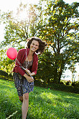 Smiling woman carrying balloons