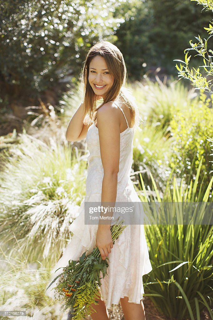 Smiling woman carrying bouquet of flowers outdoors : Stock Photo