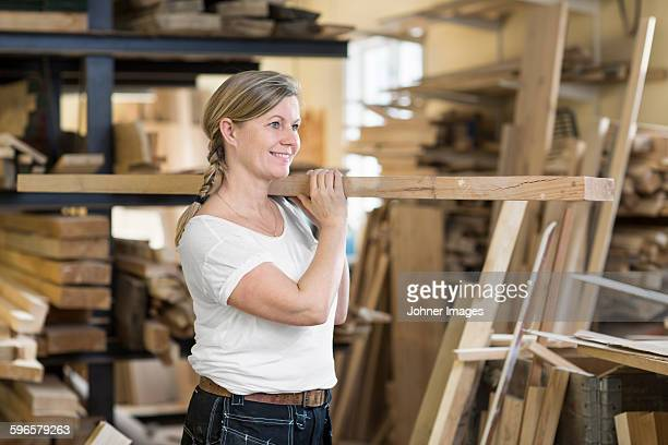 Smiling woman carrying plank