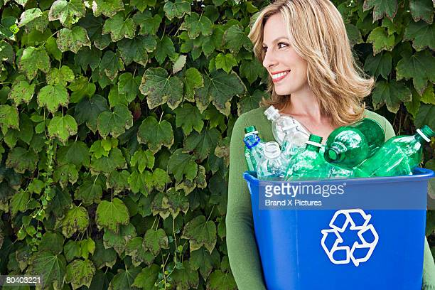 Smiling woman carrying recycling bin