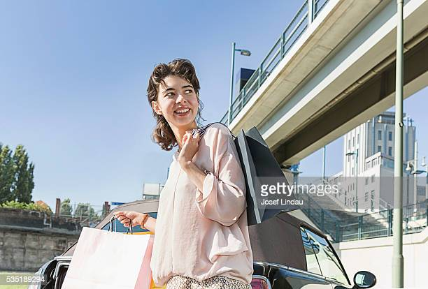 Smiling woman carrying shopping bags to her car