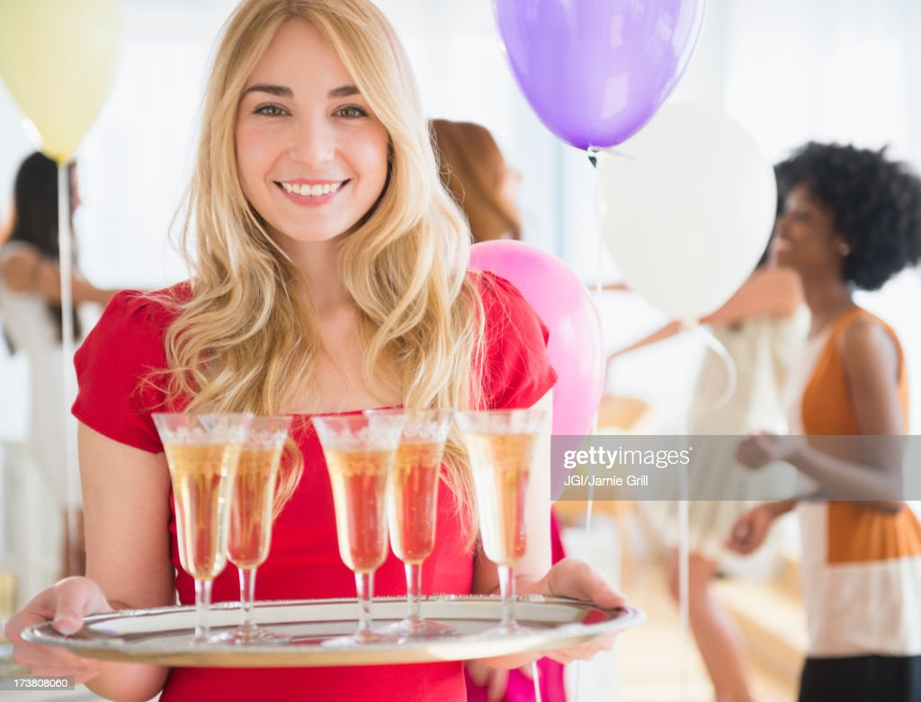 Smiling woman carrying tray of champagne