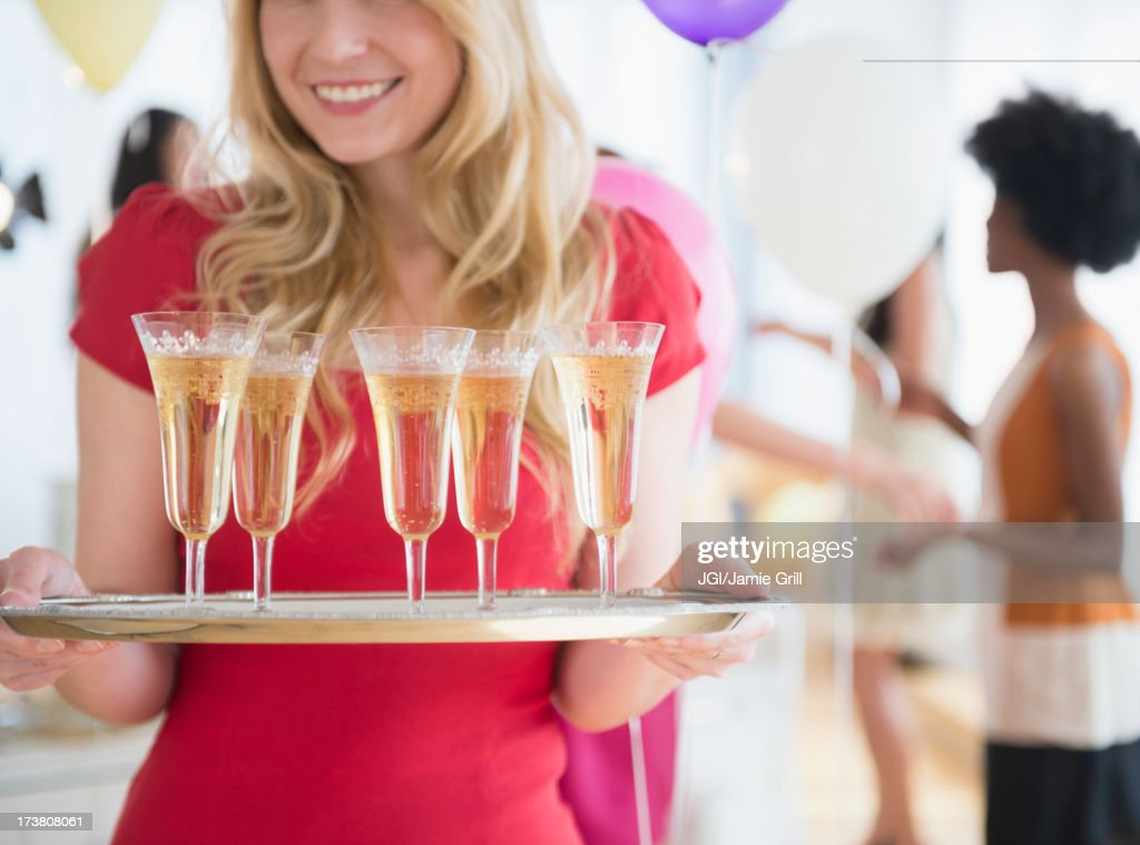 Smiling woman carrying tray of champagne : Stock Photo