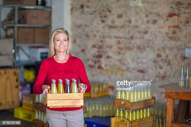 Smiling woman carrying wooden box with various bottles of juice in warehouse