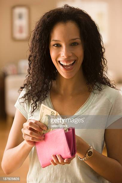 Smiling woman checking cash in wallet