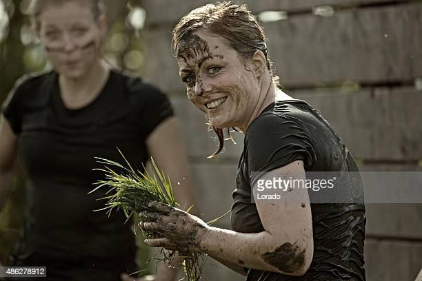 Lächelnd Frau Reinigung Ihr Gesicht mit Gras Schlamm