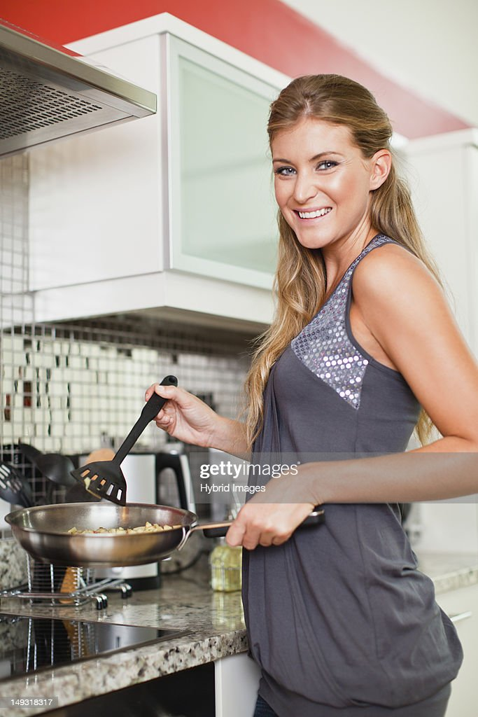 Smiling woman cooking in kitchen : Stock Photo