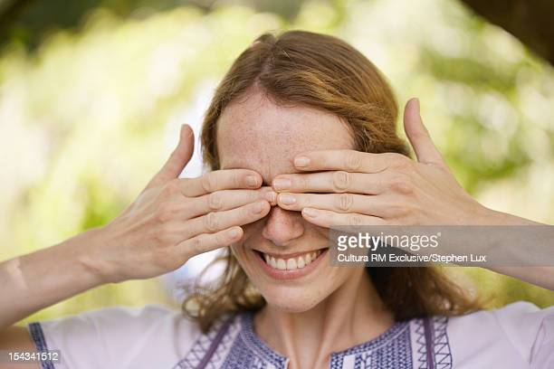 Smiling woman covering her eyes