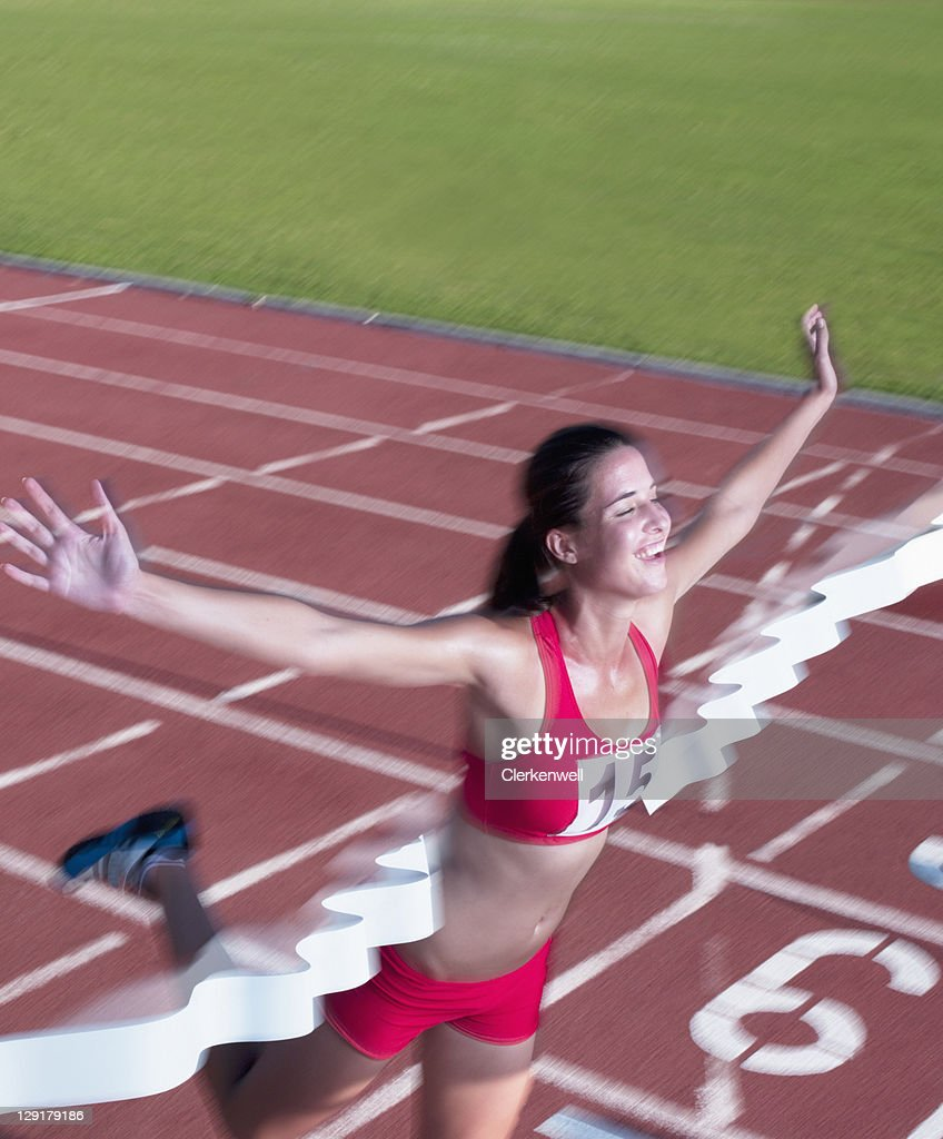 Smiling woman crossing finish line : Stock Photo