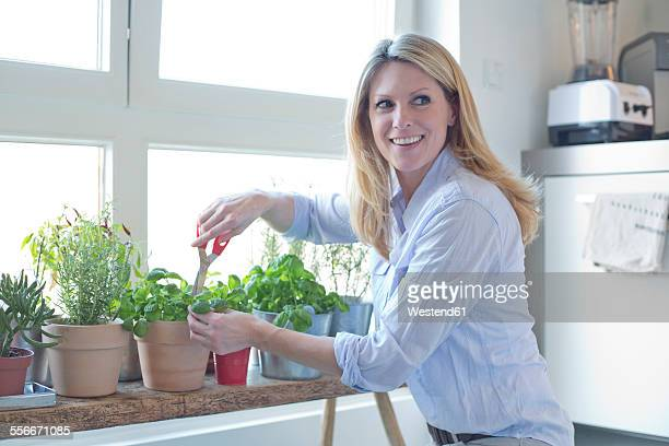 Smiling woman cutting herbs at the window