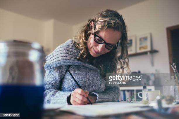 Smiling woman doing illustration.