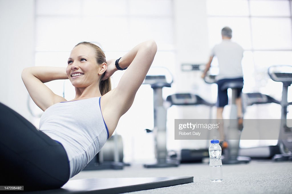 Smiling woman doing sit-ups in gymnasium : Stock Photo