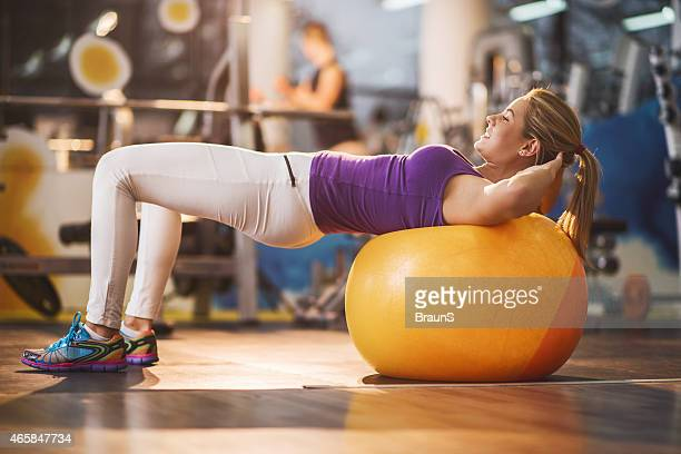 Smiling woman doing sit-ups on fitness ball.