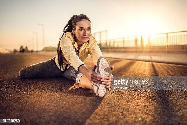 Smiling woman doing stretching exercise at sunset.
