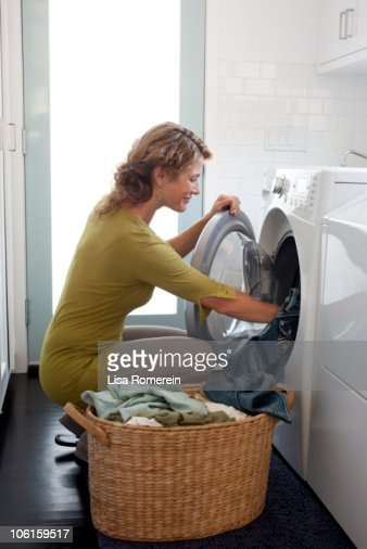 Smiling woman doing the laundry : Stock Photo