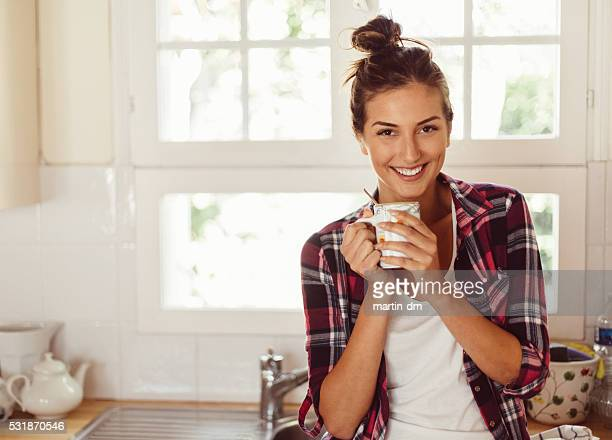 Smiling woman drinking coffee early in the morning