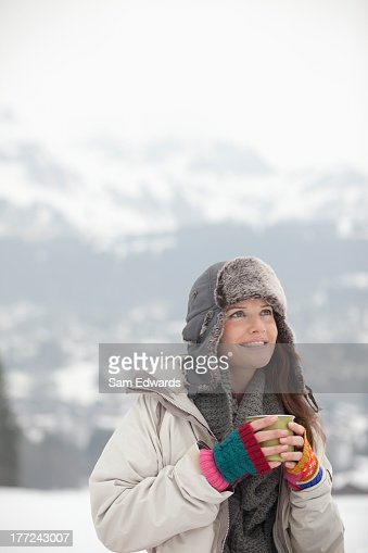 Smiling woman drinking coffee in snowy field