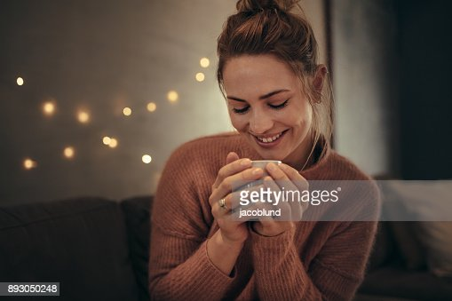 Smiling woman drinking coffee in winter at home : Stock Photo
