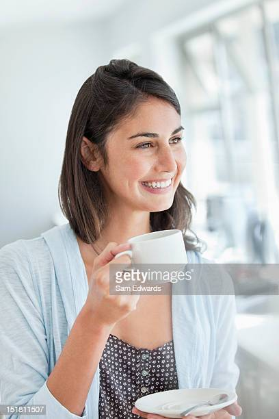 Donna sorridente bere caffè