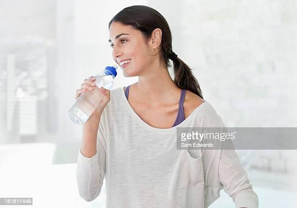 Lächelnde Frau trinkt aus Flasche Wasser