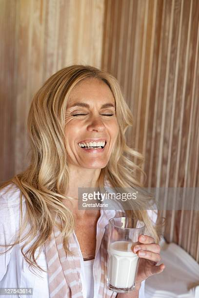 Smiling woman drinking glass of milk