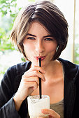 Smiling woman drinking through straw
