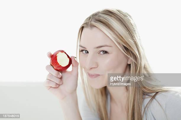 Smiling woman eating apple