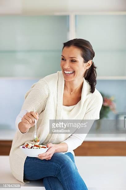笑顔の女性のサラダを食べにカウンター