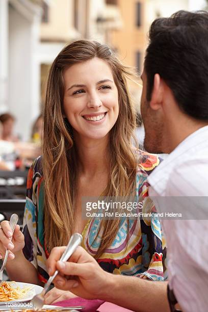Smiling woman eating in pavement cafe