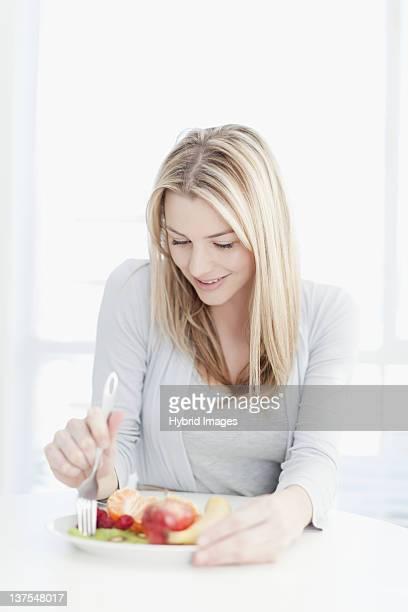Mulher sorridente a comer placa de alimentos