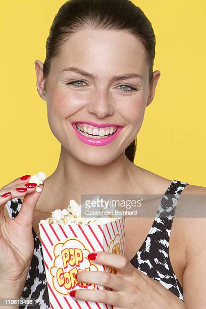 smiling woman eating popcorn