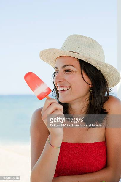 Smiling woman eating popsicle outdoors