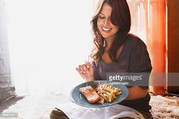 Smiling woman eating salmon and pasta