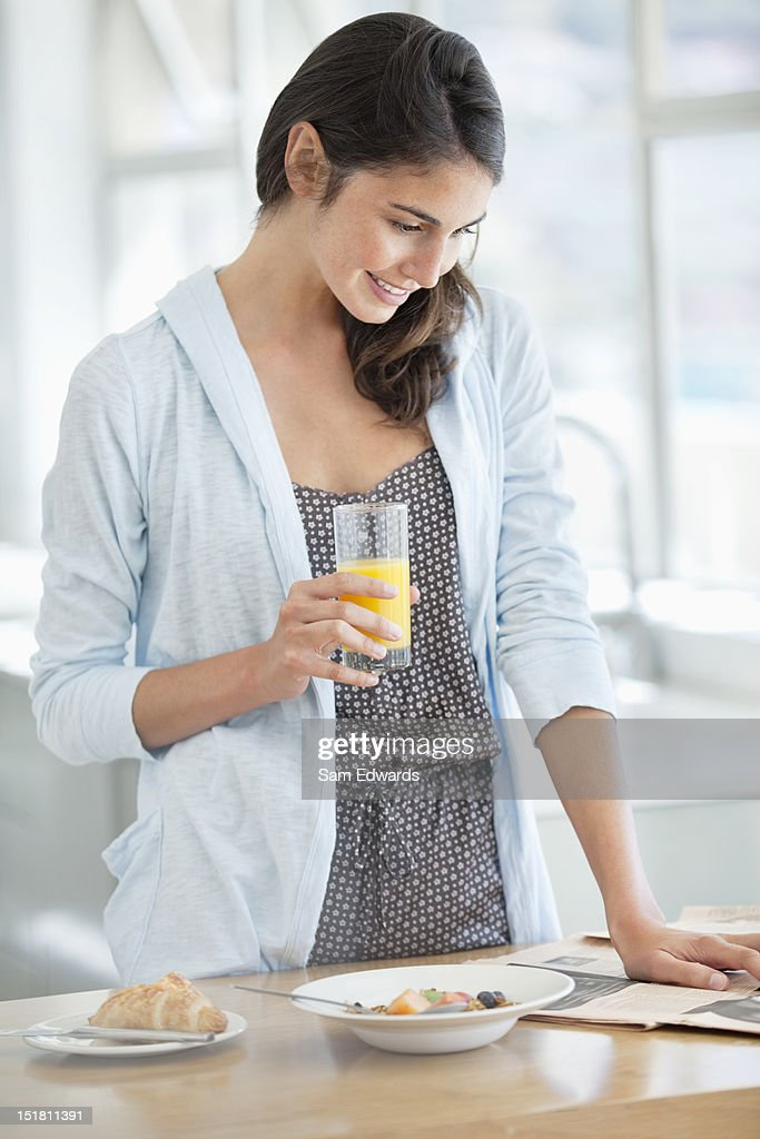 Smiling woman enjoying breakfast and reading newspaper : Stock Photo