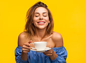 Cheerful pretty woman enjoying coffee with eyes closed on yellow background.
