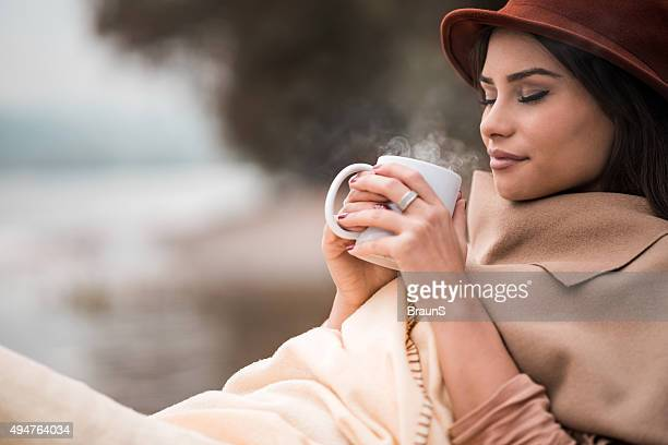 Smiling woman enjoying in a smell of hot chocolate outdoors.