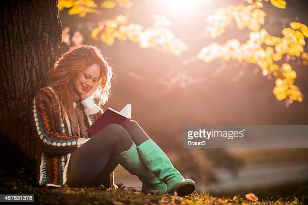 Smiling woman enjoying in autumn day while reading a book.